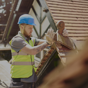 man wearing hard hat working on a tile roof